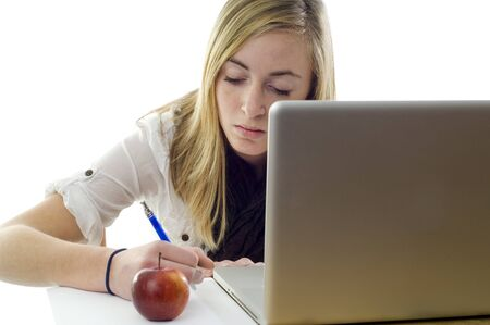 Teenage girl uses her laptop, pen and papers to complete her homework.