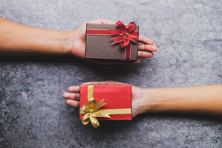 Women hand holding brown gift box And a red gift box given to each other on a gray stone table