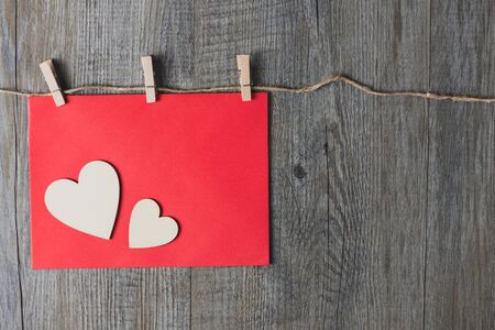 A wooden heart placed on a red envelope And placed on a gray wooden background