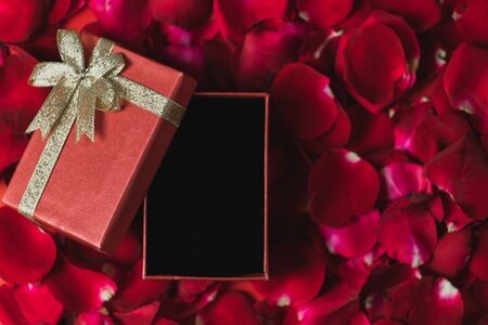 赤いギフトボックス 赤いバラの花びらに置かれた トップビュー、バレンタインデーのテーマ