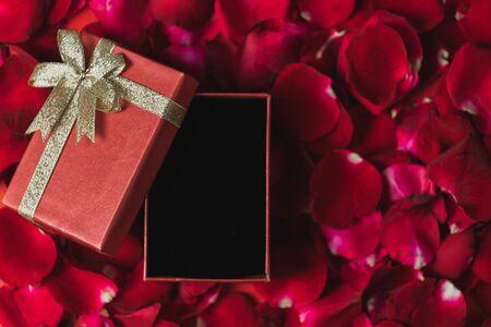 Rode geschenkdoos Geplaatst op rode rozenblaadjes Bovenaanzicht, Valentijnsdag thema
