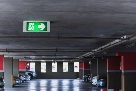 Close up of the fire exit signs attached to the ceiling in the parking building Stock Photo