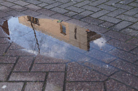 clinker tile: Reflection of a house in a puddle