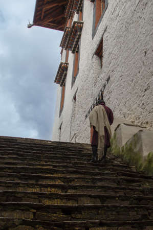 religious clothing: Man in traditional clothing on stairs in dzong in Bhutan