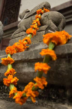 god's cow: A marigold garland on a statue on durbar quare Kathmandu