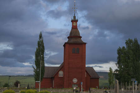 A Swedish falu red church just before a storm
