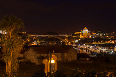 dom: The monastry do Serra do Pilar and the bridge of Dom Luis I lit up at night in Porto