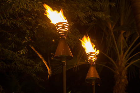 Polynesian torches lit at night in Waikiki