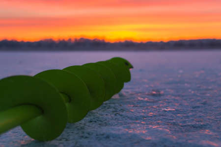 Fishing ice auger at dawn fishing drill ice beautiful sky