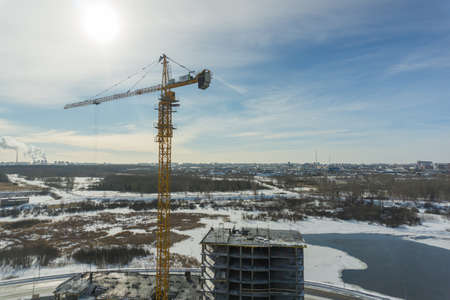 Crane builds a house construction in winter Siberia Russia