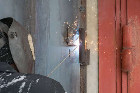 welding a man repairs a garage outdoors