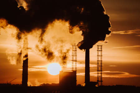 smoke of the factory chimneys environment pollution in the sunset of an industrial city