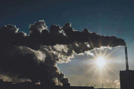 smoke of the factory chimneys environment pollution in the sunset of an industrial city Standard-Bild