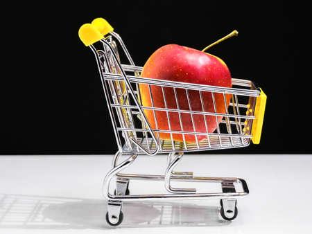 concepto de carro de supermercado de alimentación saludable. manzana roja. Foto de archivo