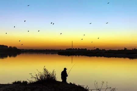 silhouette of a fisherman at sunset in summer on the river fishing Фото со стока