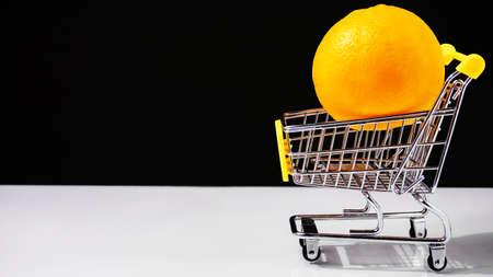 Carrito de compras comprando naranjas concepto de comida sana Foto de archivo