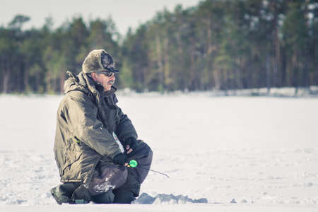 man catches a fish in the winter