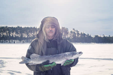 man holding catch winter fishing pike fish