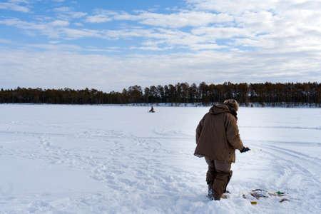 a fisherman holds the ice-fishing catch big fish bass. winter sport. Фото со стока