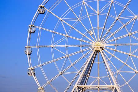 Ferris wheel in summer on blue sky amusement Park