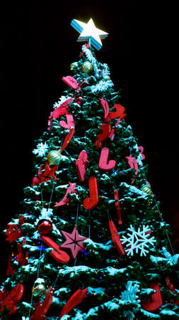 Christmas tree at night against the black sky, vertical photo. The concept of Christmas and new year, a place under the text copy space. Banco de Imagens
