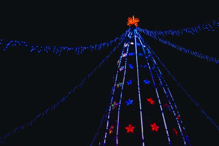 Top of the artificial Christmas tree illuminated by golden led lights against dark night sky. Winter holidays.