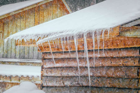 Frozen mysterious mansion with water pipe gutters and frozen icicles on the roof, top floor wooden mansion. Icy weather winter scen