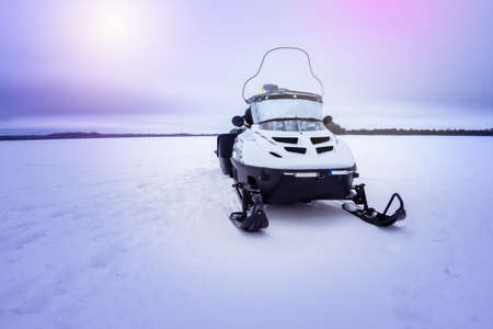 Snowmobile on the background of snow, frozen lake and cloudy sky. Winter season