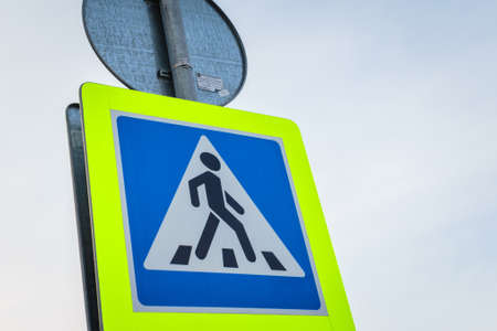Traffic sign pedestrian crossing on sky background close up