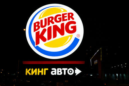 Tyumen, Russia - October 03, 2019: Burger King restaurant exterior-sign near the main entrance at night. Sale of fast food fast food