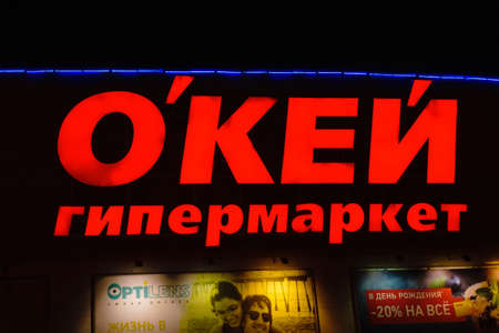 Tyumen, Russia - October 03, 2019: Signboard of the name folded from large red letters above the entrance to the store hypermarket Okay. Night photography
