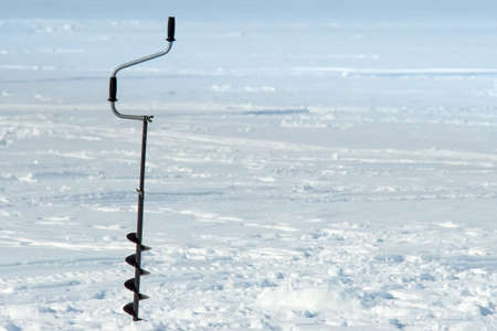 Winter fishing on ice. Drilling a hole in the ice. Winter sport winter fishing place under copyspace