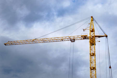 Yellow construction crane on the background of clouds construction construction of high-rise buildings 스톡 콘텐츠