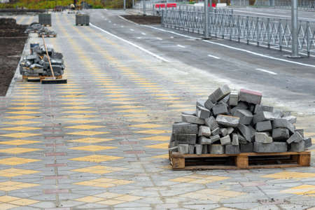 Lay granite cubes along street. Reconstruction of sidewalk with cobblestone in sand. retro-style