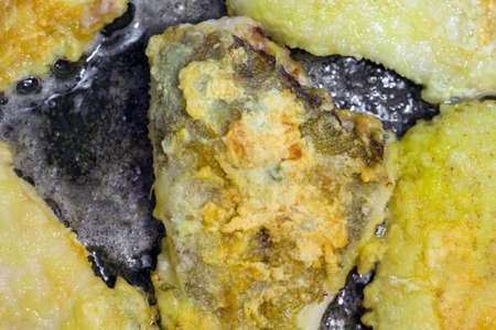 pieces of fried yellow fish flounder, fried in a frying pan. Cooking homemade food Stock Photo