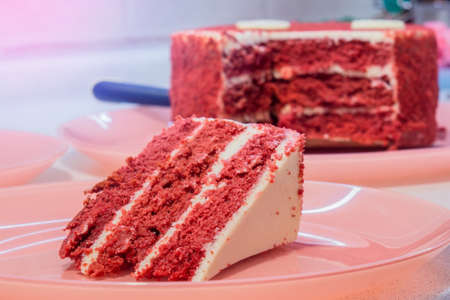 red velvet cake on a glass platter with one slice removed in front 写真素材
