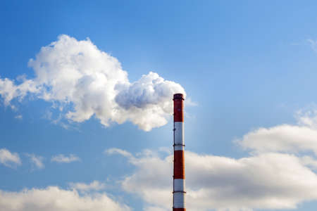 plant tubes with white smoke on blue sky, chemical plant towers of nuclear power plant against the blue sky. Air pollution
