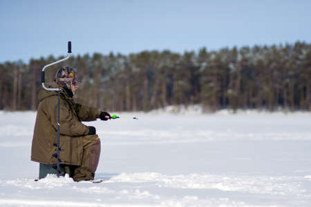 Winter fishing. Ice fisherman fishing in the winter on the river. winter fisherman sits in camouflage clothing near a hole with an ice drill on a frozen snow covered river on a winter day. Banco de Imagens