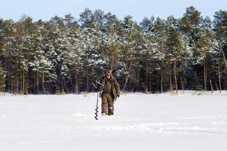 fisherman in winter, walking on a winter lake. Winter season, Siberia winter fishing