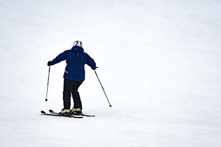 Skier quickly goes down the slope. Traffic, winter sports, winter entertainment, selective focus.