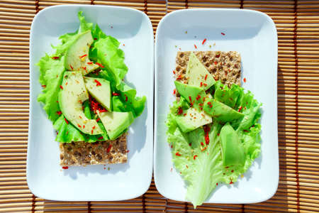 crispbread with salad and avocado on a white plate top view. Healthy healthy diet Breakfast for two