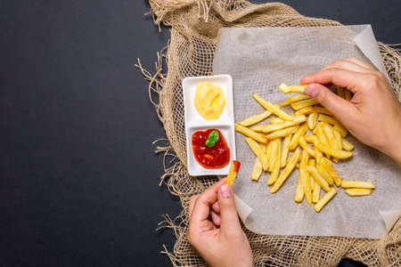 fries-fried potatoes with cheese sauce, ketchup on a black background with cheese sauce. vertical photo