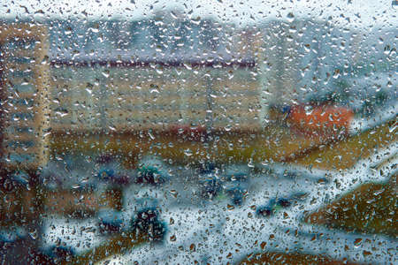 Rain falls on the surface of window panes with a cloudy background. raindrops highlighted on a cloudy background.