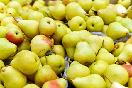 Fresh delicious organic yellow pears on the shelves of the hypermarket background.