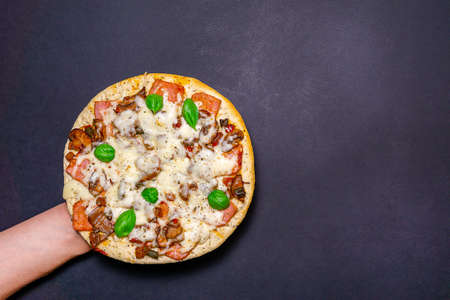 pizza with mushrooms, Basil and cheese on a dark background. copy space. The view from the top. flat lay. Фото со стока