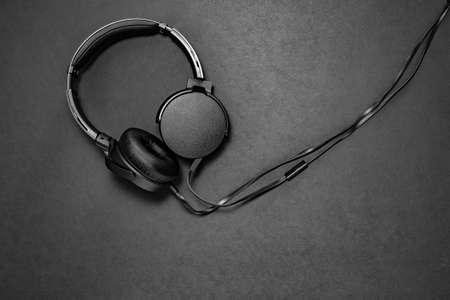 Black headphones on black matte background. Minimalistic composition topview. space for text, free space Фото со стока