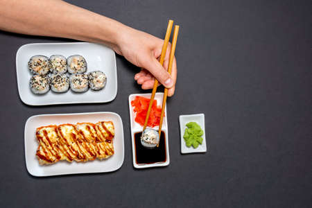 Top view on traditional japanese sushi, ginger, soy sauce, rustic black background, copy space