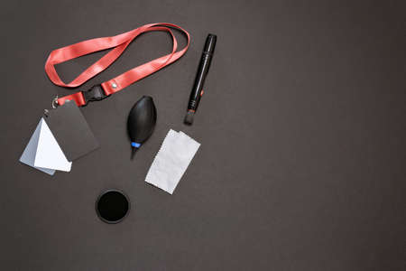 accessories for the photographer on a black background, a gray map, a napkin, a dust bag, a polarizing filter. the view from the top, flat lay Фото со стока - 150787543