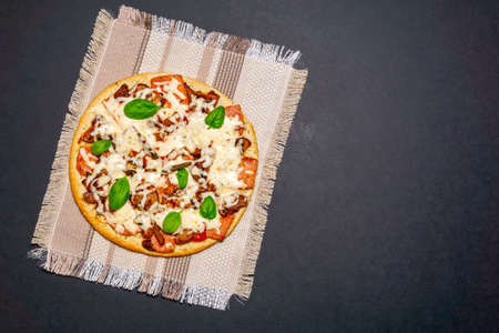 Homemade pizza with mushrooms, Basil and cheese on a dark background. A copy of the space. The view from the top. flat lay Фото со стока