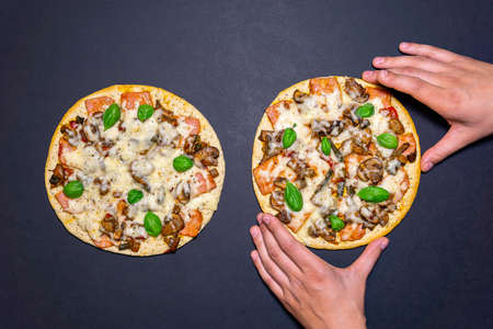 Pizza on a black concrete background. mozzarella, mushrooms, Basil. Copy space for text. the view from the top, flat lay Фото со стока